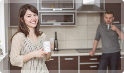 Man and woman drinking coffee in remodeled kitchen